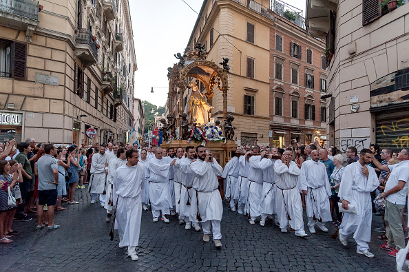 ROME, ITALY - JULY 22: The bearers carry the statue for the Solemn celebrations and procession in honor of Madonna del Carmine, Our Lady of Roman Citizens, called 'de 'Noantri', took place to Trastevere on July 22, 2017 in Rome, Italy. The bearers of the statue weighing 1,6 tons, are the Venerable Confraternity of the Blessed Sacrament and Maria del Carmine in Trastevere. The feast was officially instituted in 1927, but the origins date back to the 16th century. In 1535, after a violent thunderstorm, a statue of Mary carved out of cedar wood washed up on the shores of the Tiber. She was brought up the river and given to the then Carmelite church of St. Chrysogonus. (Photo by Stefano Montesi - Corbis/Corbis via Getty Images)