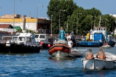 ROME, ITALY - JULY 30: A boat carries the Madonna fiumarola 'river Mary,' down Tiber river in Fiumicino, city lies on the northern side of the mouth of the Tiber River, during the procession along Rome's Tiber River as part of the traditional Festa di Noantri on July 30, 2017 in Rome, Italy. The feast was instituted in 1927, but its origin dates back to the 16th century. In 1535, after a violent thunderstorm, a statue of Mary carved out of cedar wood washed up on the shores of the Tiber. She was brought up the river and given to the then Carmelite church of St. Chrysogonus. (Photo by Stefano Montesi - Corbis/Corbis via Getty Images)